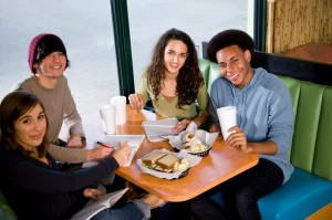 Multi-ethnic teenagers having lunch together in restaurant